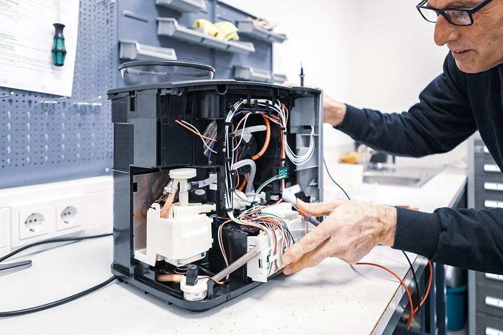 Abbildung Mitarbeiter repariert Maschine